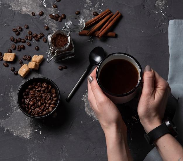 Mano prendere la cannella scura del caffè espresso di vista superiore dei fagioli del fondo di caffè