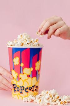 La mano prende un popcorn da un bicchiere di carta su una rosa