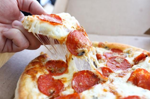 La mano prende la pizza intera calda del formaggio della fetta dalla scatola.