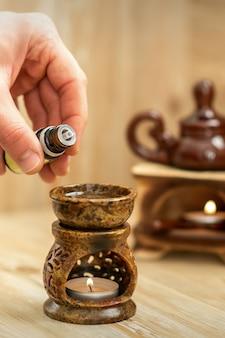 Mano del terapista versa gocce di olio essenziale al diffusore in ceramica nel salone della stazione termale
