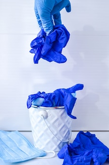 Mano che butta via maschere infettive usate e guanti medici nel cestino della spazzatura. cestino del coronavirus. rifiuti medici covid-19. dispositivi di protezione individuale usati dpi. inquinamento da plastica dopo la pandemia