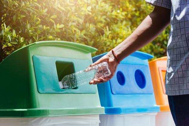 Mano che getta una bottiglia d'acqua in plastica vuota nel cestino dell'immondizia