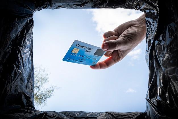 La mano getta la carta di credito nel cestino con il pacchetto su sfondo blu, vista dal basso. concetto di abbandono di transazioni bancarie e prestiti finanziari.
