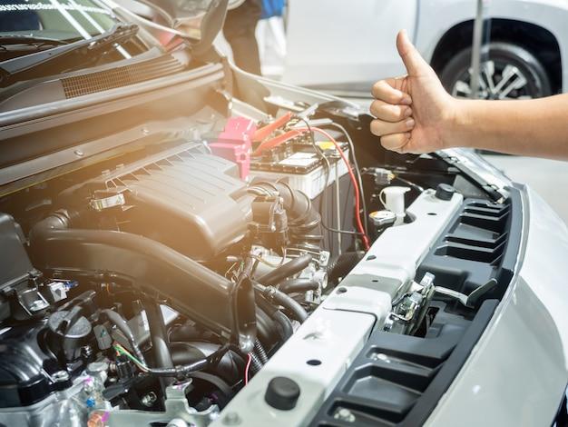 Pollice in su con l'interno della macchina del motore dell'auto pulito e lucido con il bagliore di luce del pollice in alto