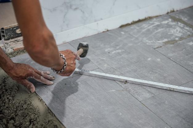 Mano del piastrellista che posa e usa la mazza battendo le piastrelle di granito sul pavimento