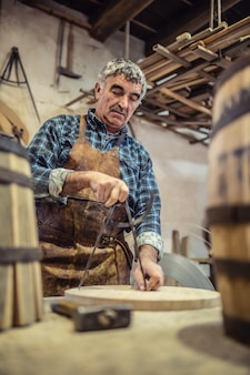 Strumenti manuali utilizzati per misurare e assemblare prodotti in legno da un artigiano anziano.