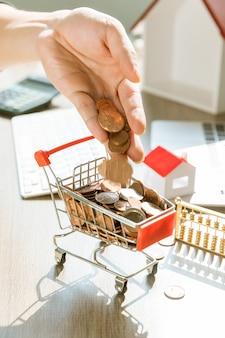 Mano lanciare monete in un carrello della spesa giocattolo pieno di monete su una scrivania