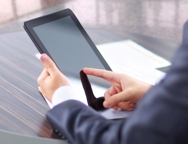 Mano che tocca il moderno tablet pc digitale sul posto di lavoro.