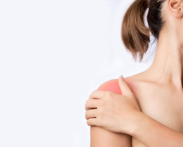Mano che tocca l'articolazione della spalla su sfondo bianco giovane donna che tiene l'articolazione della spalla