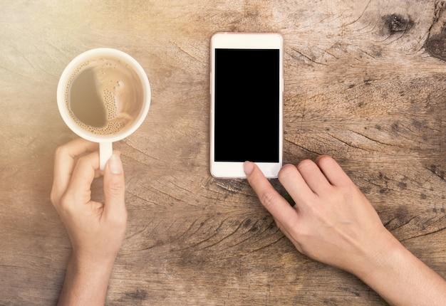 Mano che tocca lo smartphone e tiene la tazza di caffè