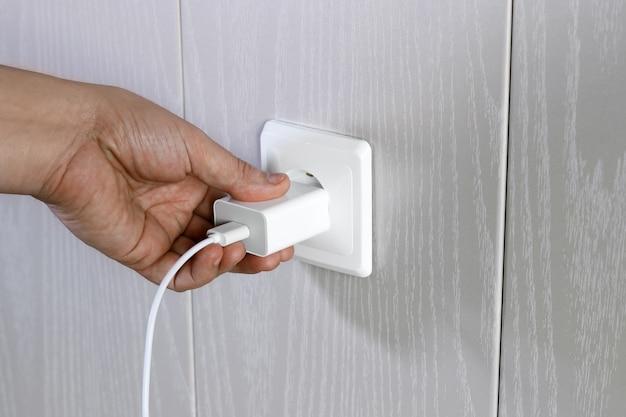 La mano si accende, spegne il caricabatterie nella presa elettrica a muro