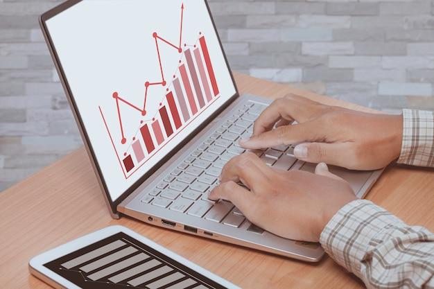 Passi la battitura a macchina sul computer portatile con un grafico crescente, concetto di lavoro.