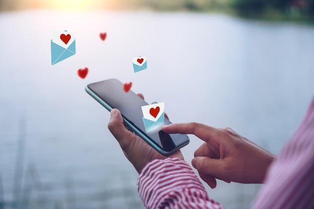 Mano che digita il email della lettera di amore nella comunità online della rete sociale dello smartphone con la posta della lettera di amore di media sociali invia il concetto di san valentino delle icone.