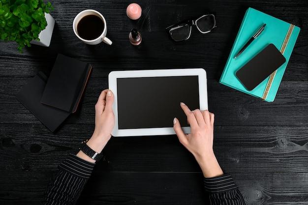 Mano usa tablet bianco sul tavolo scrivania. vista dall'alto di mani umane, tablet, una tazza di caffè, smartphone, notebook e un fiore su uno sfondo di tavolo in legno.