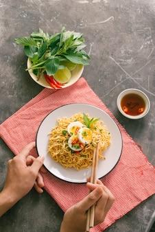 La mano usa le bacchette per raccogliere gustosi noodles