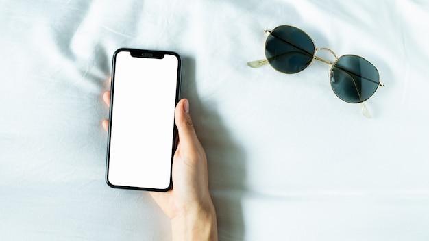 Mano con schermo vuoto dello smartphone in camera, durante il tempo libero.