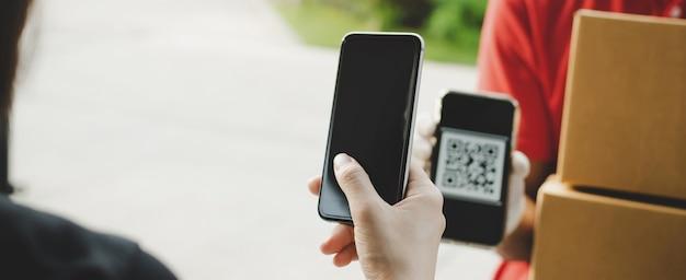 Mano utilizzando il codice qr di scansione del telefono cellulare digitale che paga per ricevere la casella postale dei pacchi