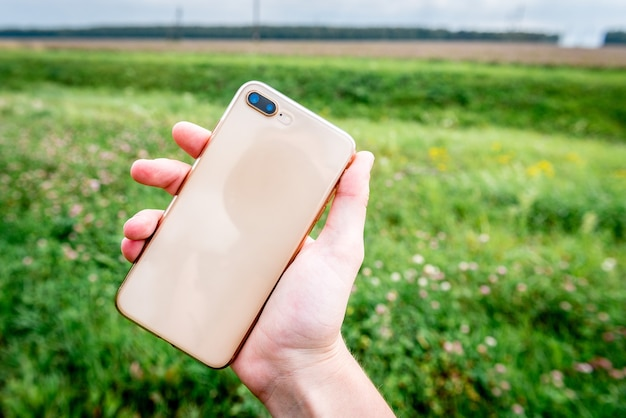 Mano utilizzando un telefono su un'erba