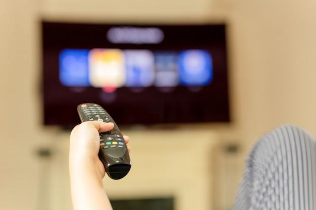 Mano usando il telecomando per guardare la televisione a casa Foto Premium
