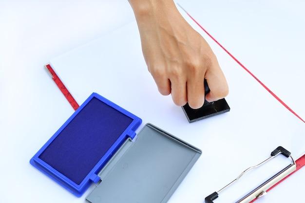 Mano usando la matrice di gomma con tampone di inchiostro blu (scatola) su carta bianca.