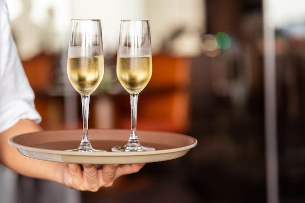 La mano del cameriere porta bicchieri con champagne su un vassoio.