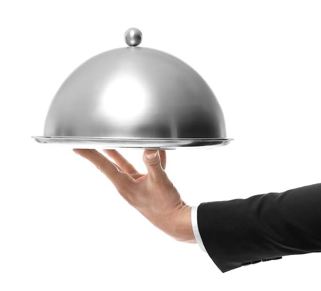 Mano del cameriere tenendo il vassoio in metallo con coperchio su sfondo bianco