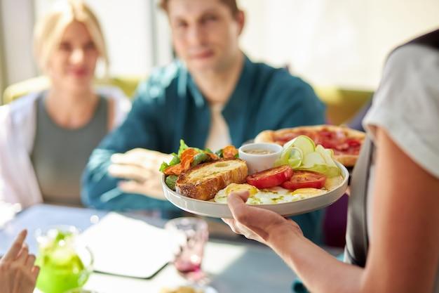 Mano del cameriere che serve il pranzo al ristorante