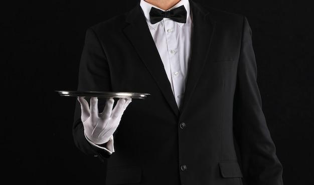 Mano di un cameriere con un vassoio su sfondo nero