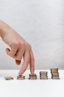 Mano che cammina sul concetto di monete