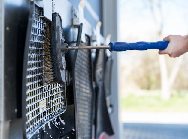 Lavare a mano tappeti di gomma dall'auto usando un pennello con schiuma