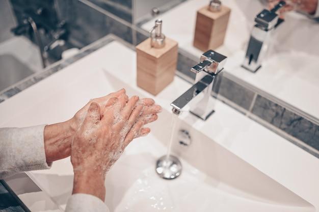 Lavaggio a mano schiuma di sapone liquido sfregamento polsi lavare a mano donna senior passo risciacquo in acqua al lavandino del rubinetto del bagno.