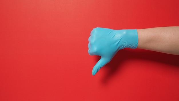 Indossare a mano un guanto chirurgico e fare il pollice verso il segno della mano su sfondo rosso. si usa quando non ti piace qualcosa.