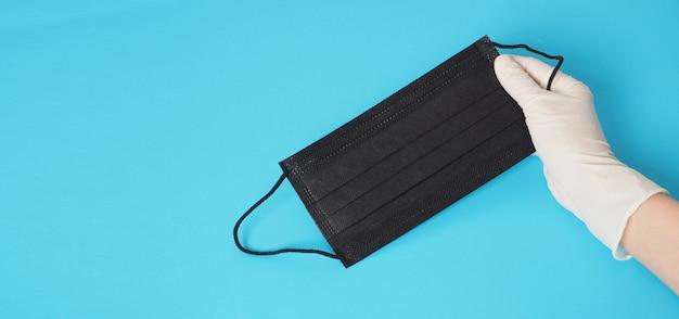 Il guanto bianco da indossare a mano tiene in mano una maschera nera per la protezione da infezioni virali e sostanze chimiche. metti su sfondo blu.