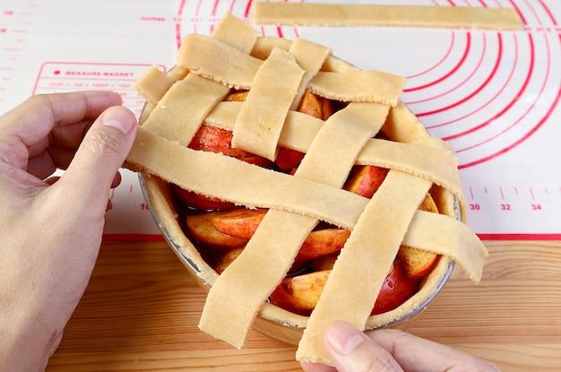 Tessitura a mano di pezzi di pasta tagliata sul piatto della torta per la crosta superiore del reticolo di una torta di mele fatta in casa