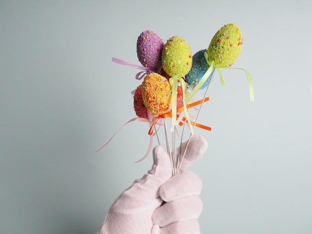 Una mano in un guanto bianco tiene un mazzo di uova colorate.
