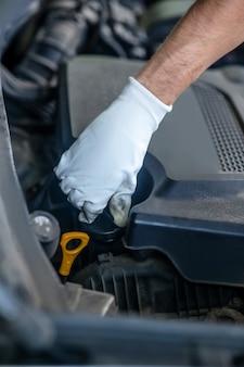 Mano nel guanto protettivo bianco che esegue l'azione di torsione sotto il cofano aperto dell'auto