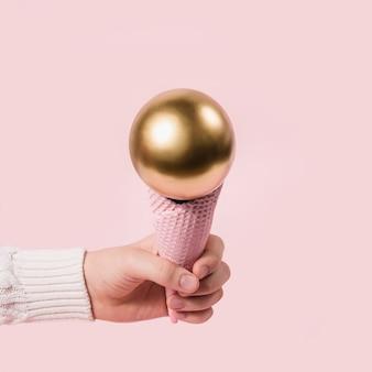 La mano in maglione bianco tiene un cono gelato rosa con palla dorata. il minimo concetto di natale.