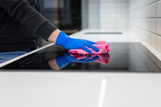 La mano pulisce la stufa elettrica con uno straccio.