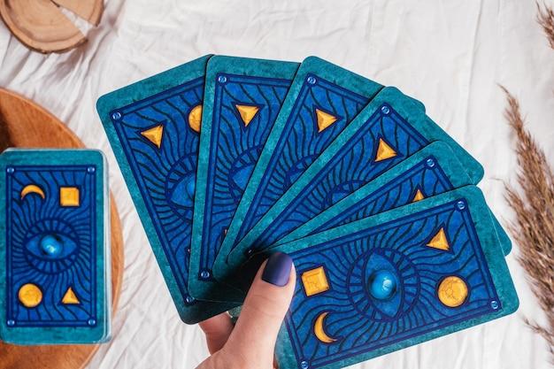 La mano con le unghie blu tiene le carte dei tarocchi a ventaglio su un foglio di stoffa bianca con spighette. minsk, bielorussia - 27.09.2021