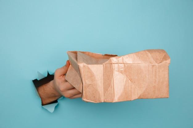 Mano con una scatola di consegna rotta attraverso un foro di carta. incidente della spedizione.