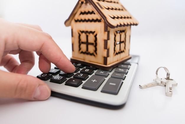 Mano con calcolatrice, chiavi dell'appartamento, casa in legno su uno sfondo bianco.