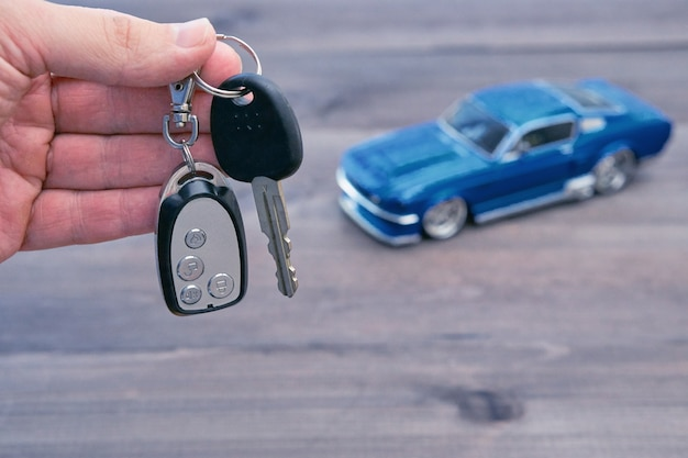 Mano con chiavi della macchina e modello di auto piccola