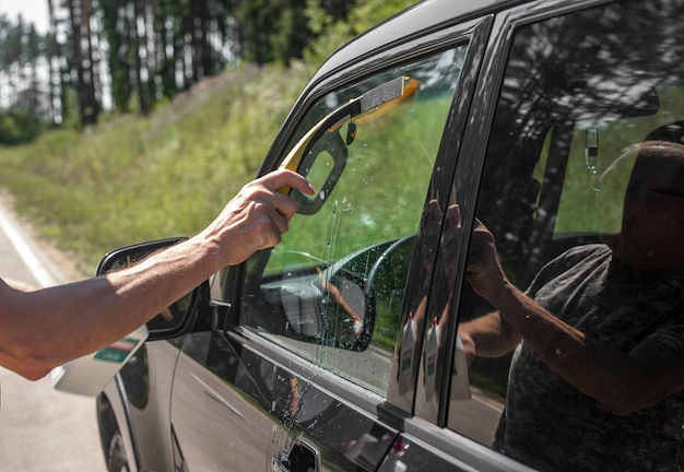 Mano con tergicristallo in gomma per auto che pulisce il finestrino dell'auto all'aperto in estate