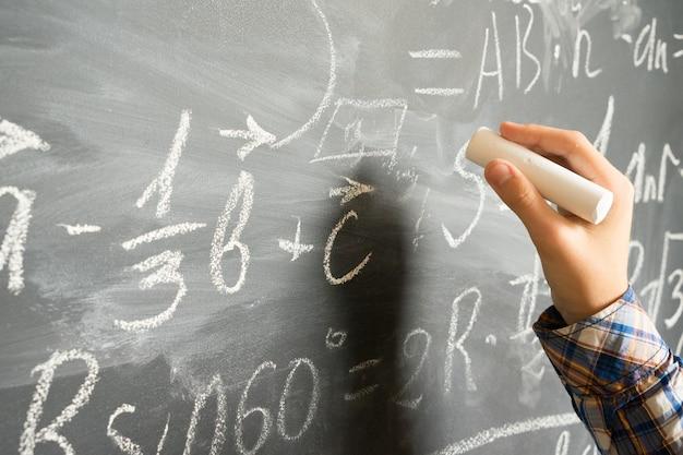 Mano con la scrittura del gesso sulla lavagna nera di formule matematiche