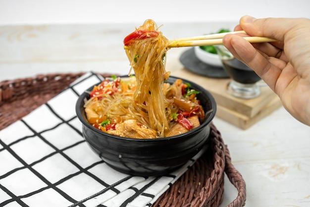 Mano con bacchette e insalata asiatica con spaghetti di riso, verdure, funghi, pollo e salsa di soia