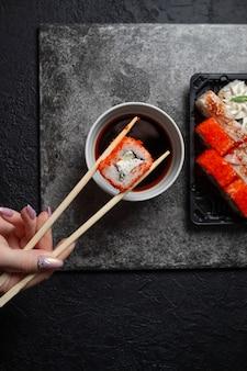 Mano con le bacchette, ristorante giapponese, piatto di rotolo di sushi su lastra di ardesia nera. set per una persona, con bacchette, zenzero, soia, vista dall'alto.