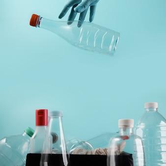 Mano con un guanto di pulizia che fa cadere una bottiglia di plastica usata nel cestino. riutilizzo, riciclaggio e concetto di campagna a rifiuti zero. cura dell'ambiente
