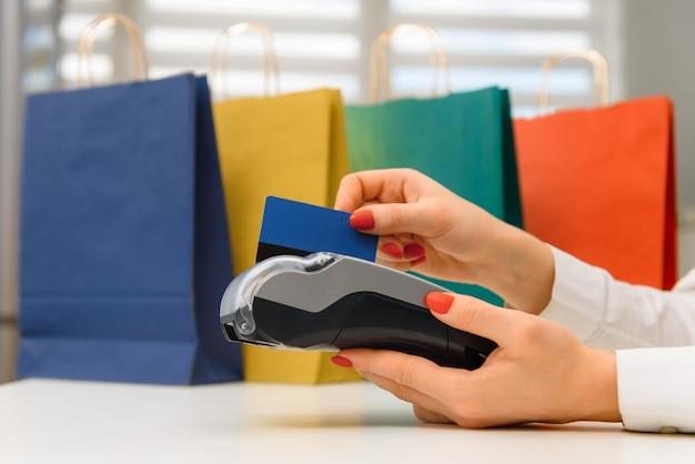 Mano con carta di credito strisciare attraverso il terminale in vendita nel supermercato