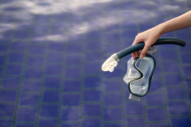 Mano con attrezzatura per maschera snorkeling in piscina.
