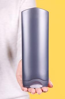 Mano con bottiglia di shampoo grigio isolata